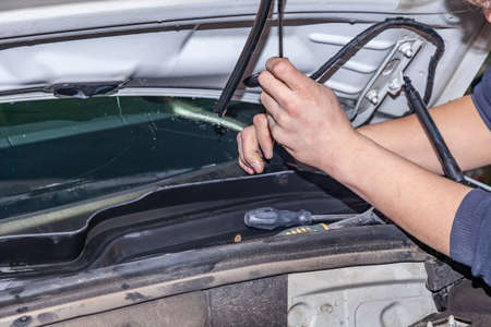 A car repairman unscrews parts windscreen wipers with a wrench with a green handle in the engine compartment in a vehicle repair workshop