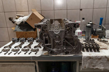 Engine connecting rods and pistons used and removed from a four-cylinder engine on a white soft cloth in a vehicle repair workshop. Auto service industry. 스톡 콘텐츠