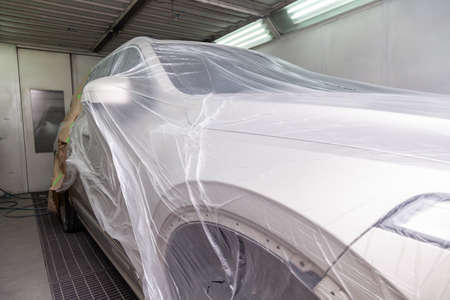 The car is a beige color covered with a transparent film to protect against the ingress of dirt and splashes from paint during body repair in the workshop for painting vehicles 写真素材