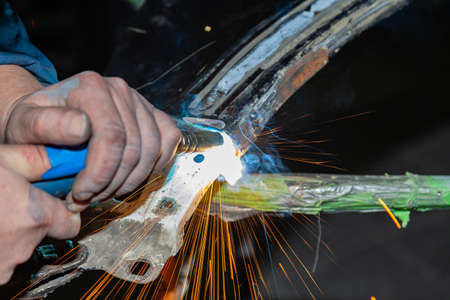 Vista ravvicinata uomo forte è un saldatore in tuta da lavoro senza guanti sulle braccia, un prodotto metallico è saldato con una saldatrice nell'officina del garage, fumo blu e scintille arancioni volano ai lati Archivio Fotografico