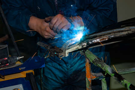 Close-up view strong man is a welder in blue working overalls without gloves on arms, a metal product is welded with a welding machine in the garage workshop, blue smoke and orange sparks fly to the sides