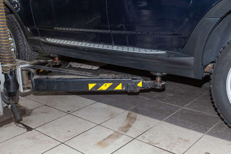 Close-up on the element of the car lift with yellow stripes under the threshold of the vehicle during repair and inspection in the service station Stockfoto