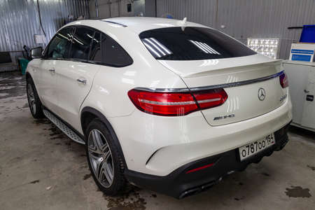 Novosibirsk, Russia - 08.01.18: Rear view of luxury very expensive new white Mercedes-Benz GLE Coupe AMG 63s car stands in the washing box waiting for repair in auto service 에디토리얼