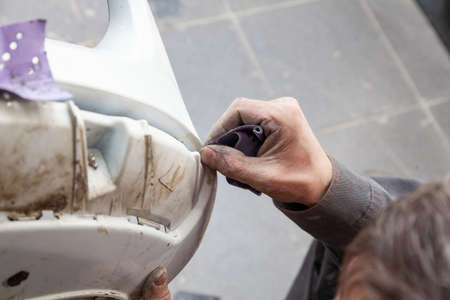A man prepares a car body element for painting after an accident with the help of abrasive paper in a car repair shop. Recovery bumper after a collision. Archivio Fotografico