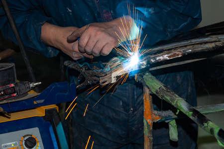 Vista ravvicinata uomo forte è un saldatore in tuta da lavoro blu senza guanti sulle braccia, un prodotto metallico è saldato con una saldatrice nell'officina del garage, fumo blu e scintille arancioni volano via Archivio Fotografico