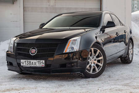 Novosibirsk, Russia - 03.10.2019: Front view of Cadillac CTS in black color after cleaning before sale in a winter day and snow background Editorial