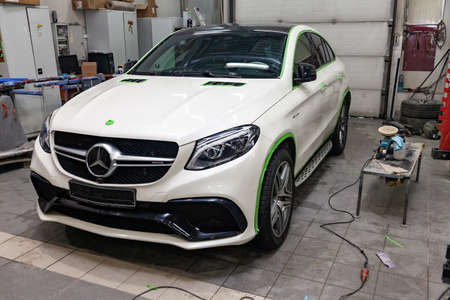 Novosibirsk, Russia - 08.01.18: Front view of luxury very expensive new white Mercedes-Benz GLE Coupe AMG 63s car stands in the washing box waiting for polish in auto service