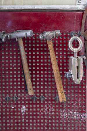 Vertical view of two old hammers with a brown wooden handle and a clamp hanging on the wall in a workshop for carpentry work on a red background