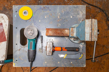 Flat lay view of a workbench with a set of tools consisting of a large heavy vise, angle grinder, screwdriver, cutter, sledgehammer, and a spare cutting disc in a workshop.