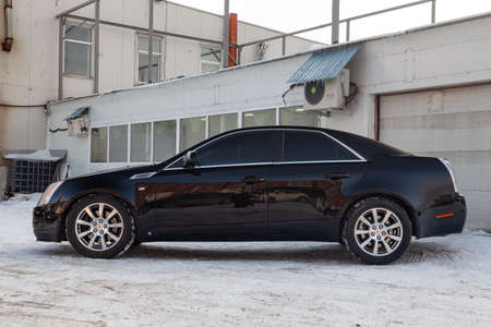 Novosibirsk, Russia - 03.10.2019: Side view of Cadillac CTS in black color after cleaning before sale in a winter day and snow background on parking