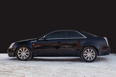 Novosibirsk, Russia - 03.10.2019: Side view of Cadillac CTS in black color after cleaning before sale in a winter day background on parking above black wall