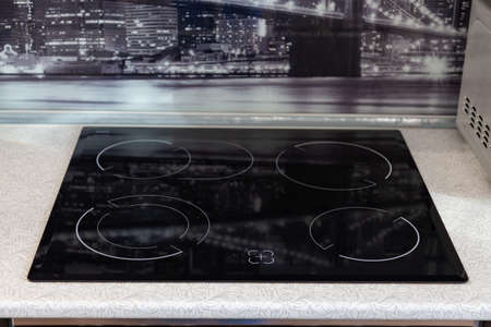 Four-burner black hob integrated into a white table with a black glass wall with a pattern in the kitchen at home