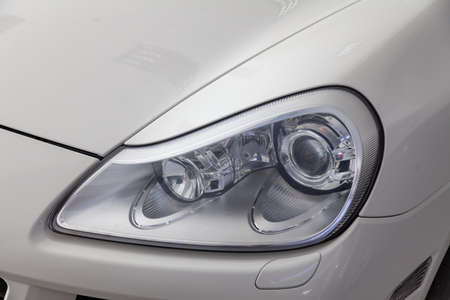 Front headlight view of car in white color after cleaning and detailing with washer before sale