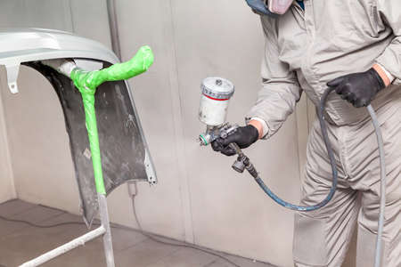 A male worker paints with a spray gun a part of the car body in silver after being damaged at an accident. Bumper from the vehicle during the repair in the workshop. Stockfoto