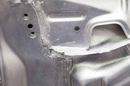 Primo piano sulla saldatura che collega le parti metalliche di un'auto di colore argento spalmato di sigillante e verniciato. Industria metallurgica.