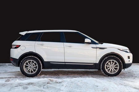Novosibirsk, Russia - 03.10.2019: Side view of Range Rover Land Rover Evoque in white color after cleaning before sale standing on snow with black wall background Editorial