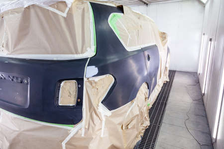 A large black car is completely covered in paper and adhesive tape to protect against splash during painting and repair after an accident in a workshop for body repair of vehicles with bright lighting