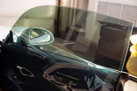 The process of tinting the glass of the car in the workshop for the installation of additional equipment with an unstuck protective film Imagens