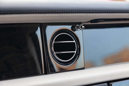 A close-up view of a part of the interior of a modern luxury car with a view of the ventilation deflector of the stove for heating and cooling the passenger compartment with black trim elements
