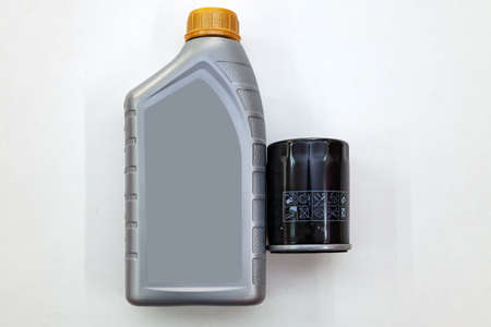 Spare part for car engine  filter for cleaning dust and dirt with one liter bottle or can of lubricant on a white isolated background. Maintenance and oil change in auto service industry.