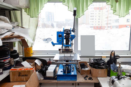 Press machine in the workshop for doing the embossed logo and letters on the leather product that heats the cliche and squeezes the desired image on the material