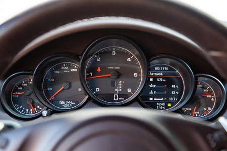 Nowosybirsk, Rosja - 04.12.2019: Wnętrze samochodu Porsche Cayenne 958 2011 rok z widokiem na kierownicę, deskę rozdzielczą, prędkościomierz, obrotomierz i kokpit z jasnobrązową skórzaną tapicerką Publikacyjne