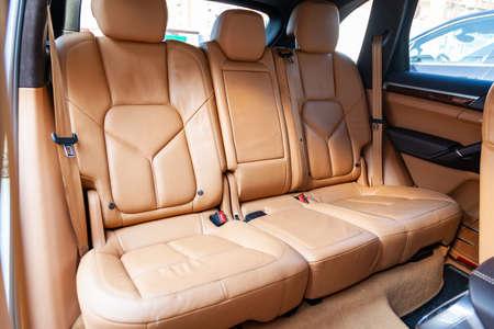 Pulire dopo aver lavato i sedili del passeggero posteriore in vera pelle marrone o beige opaca all'interno di un costoso suv di lusso, preparazione prima di vendere l'auto. Archivio Fotografico