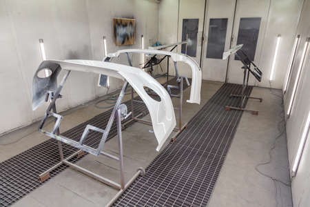 Painting and drying in a professional box of car body parts after applying putty and paint on bumper front and rear tuning spoiler and side steps in the body repair shop with white lanterns in the workshop