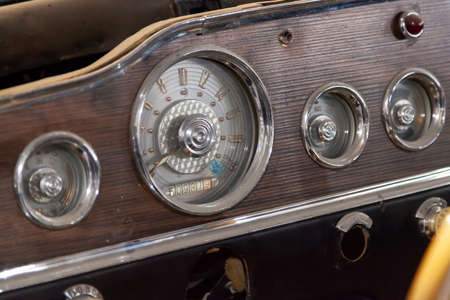 Vintage retro car dashboard with analog speedometer, tachometer and odometer, handmade with wood and chrome for restoration