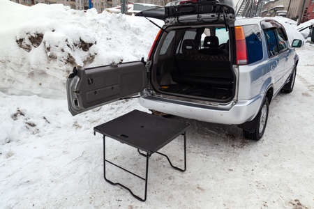 SUV car in silver color with opened trunk and table for picnic near it after cleaning before sale in a winter day and snow background