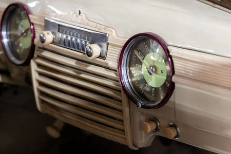 Vintage retro car dashboard with analog clock and audio radio system with buttons, handmade with wood and chrome for restoration Foto de archivo