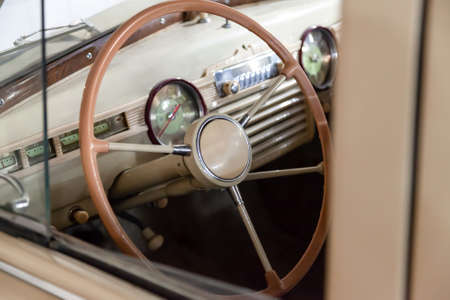 View on opened window with the steering wheel and the interior of the old Russian retro vintage car of the executive class released in the Soviet Union beige