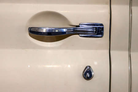 View on closed front door with handle and keyhole of the old Russian yellow retro vintage car of the executive class released in the Soviet Union