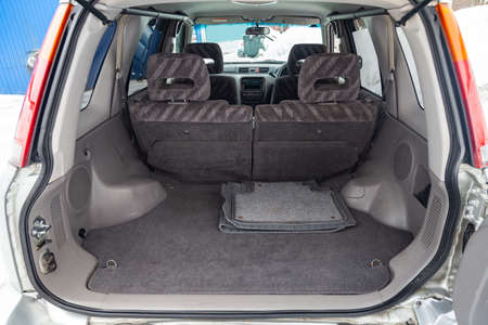 View to the gray color interior of suv car with trunk luggage compartment with striped fabric upholstery after cleaning and detailing in the vehicle repair workshop