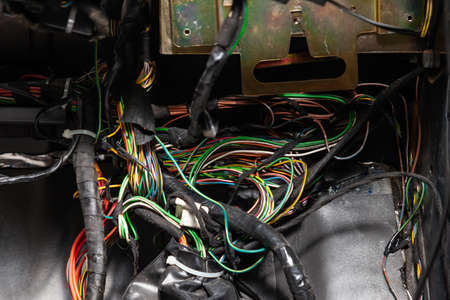 Large wide cable with multicolored red and green wires and connectors and terminals in the wiring repair shop and electricians for connecting and transmitting electricity and digital signals. Standard-Bild - 122196060