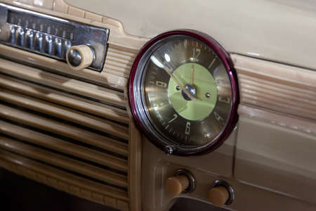 Vintage retro car dashboard with analog clock and audio radio system with buttons, handmade with wood and chrome for restoration