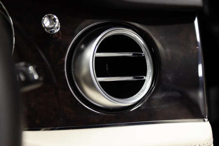 A close-up view of a part of the interior of a modern luxury car with a view of the ventilation chrome round deflector of the stove for heating and cooling the passenger compartment with black trim 免版税图像 - 122196209