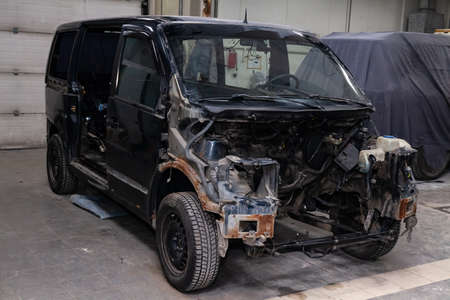 The black car in the body of the van is preparing for painting the body with the help of leveling in the places of damage to the exterior elements with rust without engine in a workshop for repair