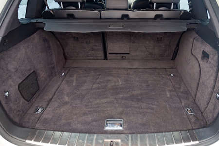 Open empty trunk of a car suv close-up after washing and vacuuming with a clean mat of special black material ready for loading luggage. Auto service industry. Imagens
