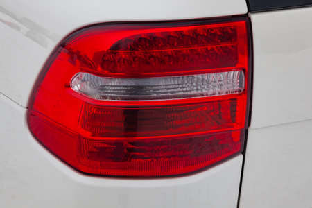 Close-up on the rear LED brake light of red color on a white car in the back of a suv after cleaning, polishing and detailing in the vehicle repair workshop. Auto service industry. Stop concept
