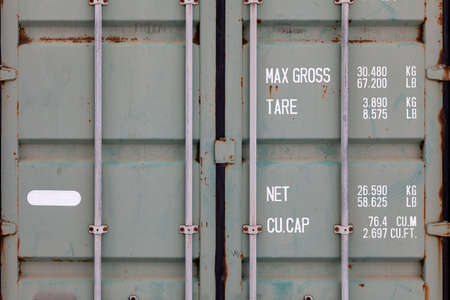 The doors of a large old container are painted in close-up in green with rust, with pipe-type locks and white lettering indicating its characteristics. Transportation and customs cargo. Archivio Fotografico