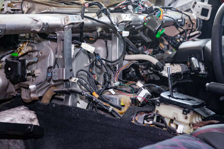 A large tangle of ravel multicolored wires from the car wiring lies in the cabin of dismantled car with connectors and plugs, a view through the window inside the battered car. Auto service industry