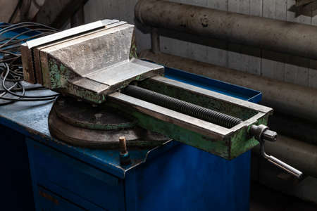 Large and powerful green vise with overwhelmed paint on a blue workbench for metal and wood work in the workshop. Repair and carpentry in the industrial and manufacturing.