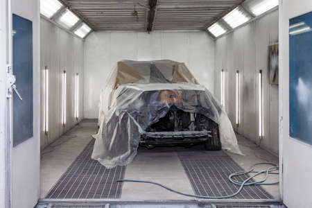 A large white car is completely covered in paper and adhesive tape to protect against splash during painting and repair after an accident in a workshop for body repair of vehicles with bright lighting Banque d'images