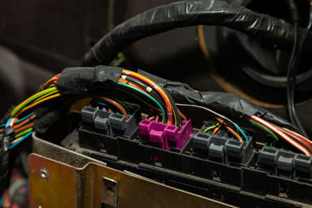 Large wide cable with multicolored red and green wires and connectors and terminals in the wiring repair shop and electricians for connecting and transmitting electricity and digital signals. Standard-Bild - 122196434