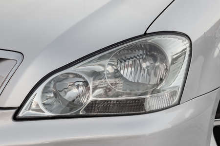 Front headlamp view of silver used car stands in the auto showroom sale after washing and polish with orange turn light and halogen lamp. Auto service industry. 免版税图像 - 122195360