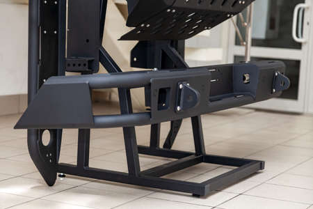 Stand for demonstration of car body elements reinforced for off-road and made of metal, such as bumper, steps and black grille in the workshop for the installation and tuning of SUV vehicles.