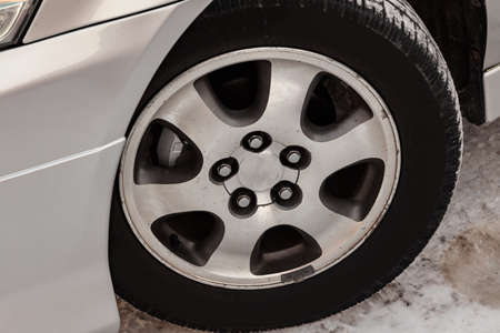 Chrome-plated cast aluminum wheel on the car with a black rubber tire, five holes for mounting bolts and six spokes through which the brake disk is visible, in the wing arch