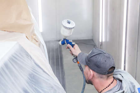 A guy worker paints with a spray gun a part of the car body in white after being damaged at an accident. Door from the vehicle during the repair in the workshop. Auto service industry professions