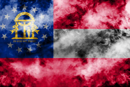 The national flag of the US state Georgia in against a gray smoke on the day of independence in different colors of blue red and yellow. Political and religious disputes, customs and delivery.